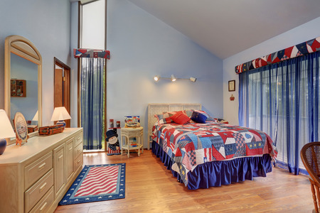 headboard: Red and blue interior of vaulted ceiling bedroom in American style with vanity cabinet and mirror, high bed with colorful bedding and white wicker headboard. Stock Photo