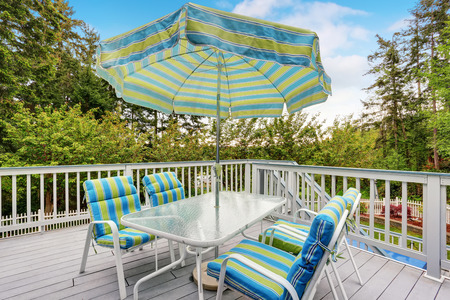 View of patio table set with umbrella in green and blue colors. Backyard view from the balcony Stock Photo