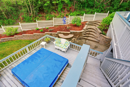 Two level backyard deck with jacuzzi on the first floor and patio area on the second one. Impressive landscape design.