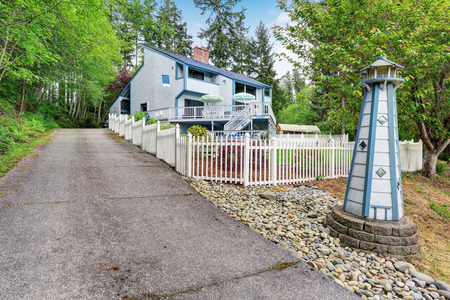 yard: Large two story marine style home with long concrete driveway. Beautiful landscape. Stock Photo
