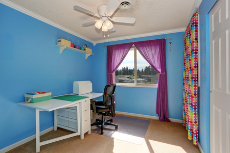Bright blue sewing room interior with colorful curtains and white table.