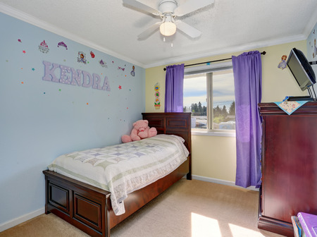 caoba: Lovely kids room in pastel blue and yellow colors, furnished with mahogany furniture set. Foto de archivo