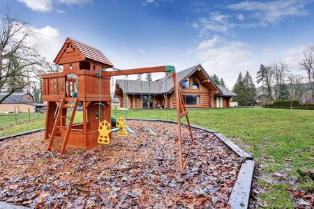 northwest: Large log cabin house exterior with kids playground. Northwest, USA