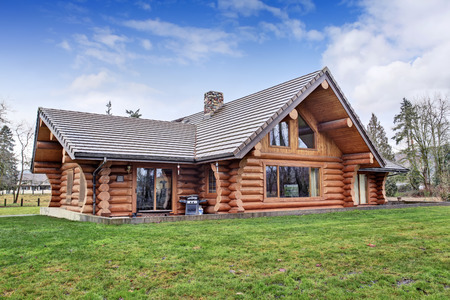 outside house: Large log cabin house exterior with grass filled back yard and small patio area. Northwest, USA