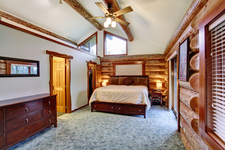 Log cabin bedroom under pitched ceiling with cherrywood furniture set. Northwest, USA.