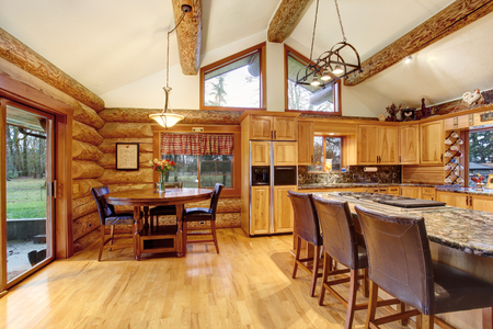Log cabin house interior of dining and kitchen room with high wooden beams ceiling. Northwest, USA.