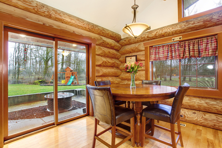Dining wooden table with leather chairs in log cabin house. Glass doors leading to back yard. Northwest, USA
