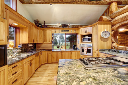 kitchen island: Log cabin kitchen interior design with large honey color storage combination and kitchen island with stone counter top. Northwest, USA