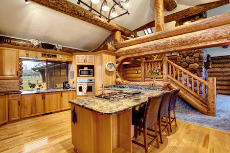 logs: Log cabin kitchen interior design with large honey color storage combination and kitchen island with stone counter top. View of staircase. Northwest, USA