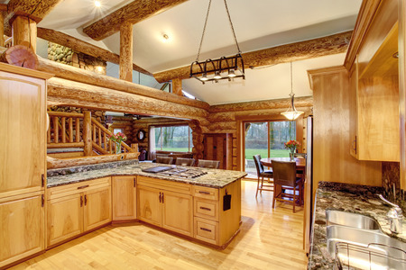 logs: Log cabin kitchen interior design with large honey color storage combination and stone counter tops. View of staircase. Northwest, USA