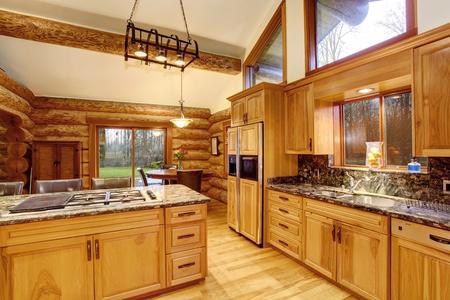 Log cuisine cabine inter design avec grande couleur miel combinaison de stockage et de comptoirs en pierre dessus. Vue de la salle à manger. Northwest, États-Unis Banque d'images - 60410697
