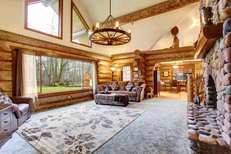 stone fireplace: Bright Living room interior in American log cabin house. Rustic chandelier, stone fireplace and high ceiling with wooden beams make room gorgeous. Northwest, USA