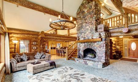 Lichte woonkamer onder in de Amerikaanse blokhut huis. Rustieke kroonluchter, stenen open haard en hoog plafond met houten balken maken kamer prachtig. Northwest, USA Stockfoto