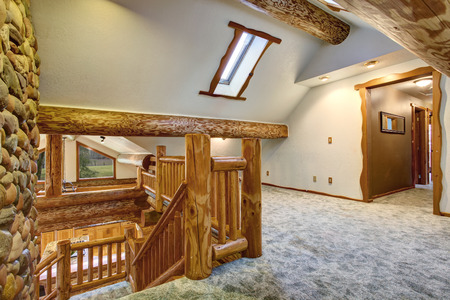 skylights: Upstairs empty room with carpet floor and pitched ceiling with skylights. American log cabin house exterior. Northwest, USA