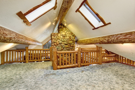 Upstairs empty room with carpet floor and pitched ceiling with skylights. American log cabin house exterior. Northwest, USA