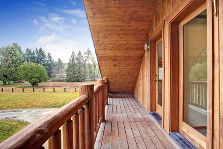 deck: American log cabin house exterior. Landscape view from the balcony. Northwest, USA