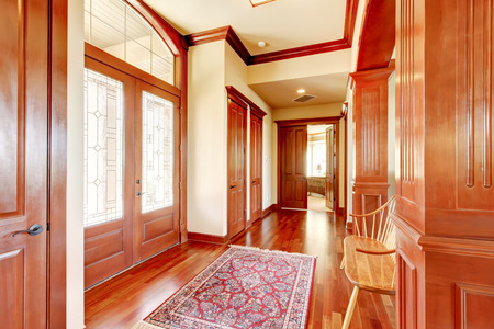 foyer: Bright foyer in luxury home with hardwood floor. Double doors with stained glass, wooden bench and colorful rug. Northwest, USA Stock Photo