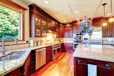 caoba: Habitación de lujo con cocina moderna combinación de almacenaje de caoba, encimeras de granito, isla y colgar macetas de rejilla. Noroeste, EE.UU..