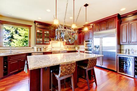 Luxury modern kitchen room with mahogany storage combination, granite tops, island and hanging pot rack. Northwest,USA.