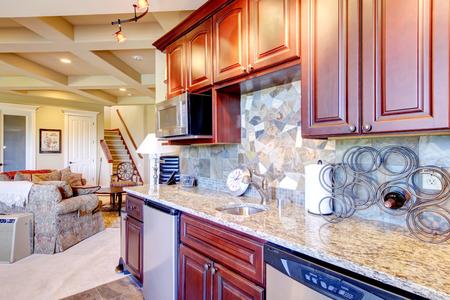 mahogany: Modern kitchen room interior with mahogany storage combination, granite tops, mosaic back splash trim, steel appliances and Metall wine rack. Northwest,USA.