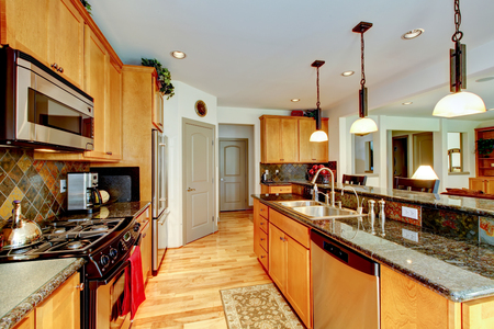 counter top: Kitchen room interior with light brown cabinets, stainless steel and granite counter top. Northwest, USA Stock Photo