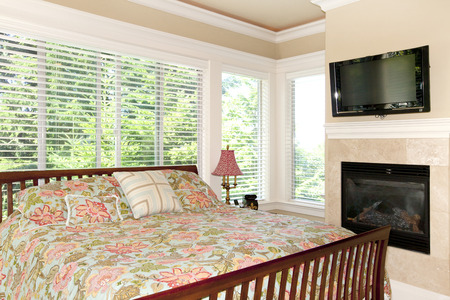 Amazing bedroom interior with fireplace and king size bed with floral bedding. Northwest, USA