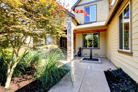 curb appeal: Exterior of American two story house with concrete walkway and nice landscape desing around. Northwest, USA