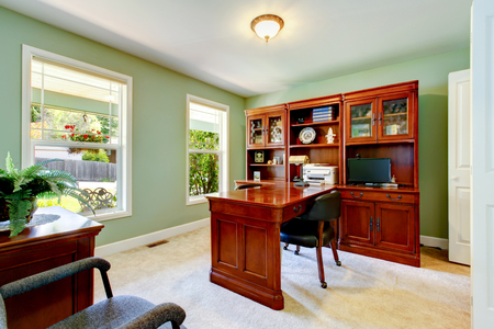 home office interior: Interior of home office with ivory walls, desk with black leather chair and cabinet. Northwest, USA