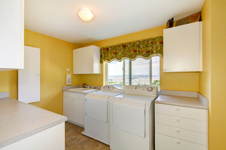 laundry room: Old laundry room with white cabinets and yellow walls. Northwest, USA