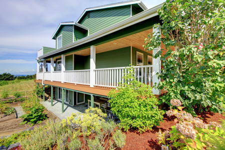 three story: Backyard view of country three story green house with large walkout deck. Small garden beds at backyard. Northwest, USA Stock Photo