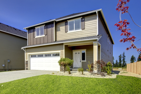 home exterior: Typical American Northwest style new development house exterior. Natural colors, simple build 3-4 bedrooms homes. First time home owners great deal. Stock Photo