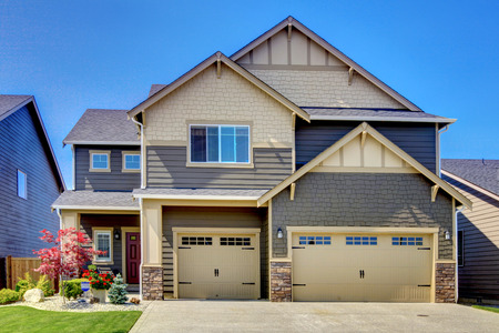 trim: Luxurious modern house with two garage spaces, driveway and stone trim. Northwest, USA Stock Photo