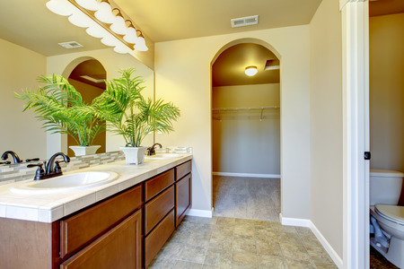 sinks: Bathroom interior in beige tones with modern brown vanity cabinet with tile top, two sinks and large mirror. Northwest, USA