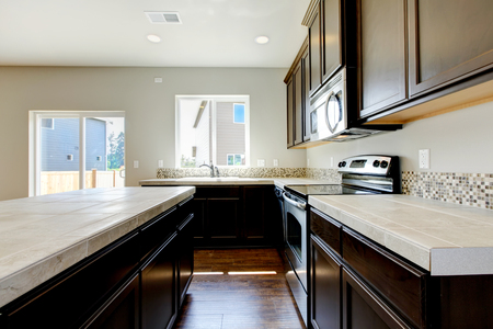 counter top: Small yet practical kitchen with black cabinets and tile marble tops. Northwest, USA Stock Photo