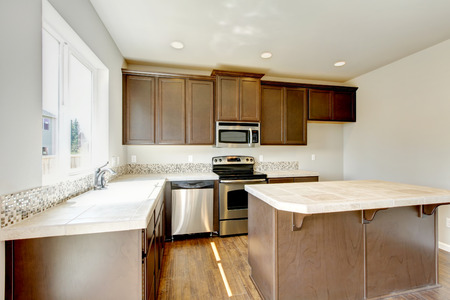cabinets: Small yet practical kitchen with brown cabinets and tile marble tops. Northwest, USA