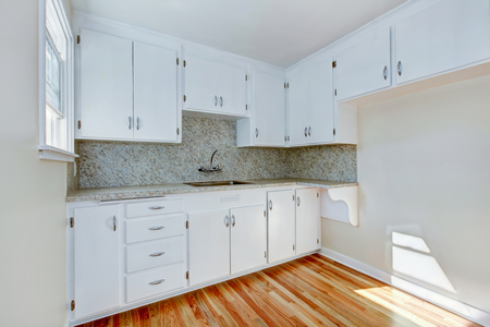 cabinets: White kitchen cabinets with steel appliances and light tone hardwood floor. Northwest, USA