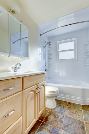 Bathroom interior with light tone vanity cabinet and tile floor. Northwest, USA