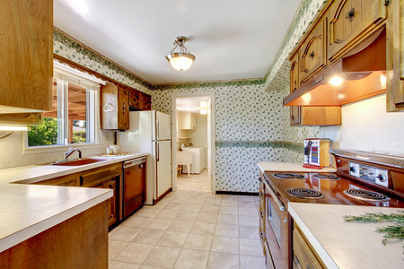 Empty simple old kitchen connected to laundry room in American rambler. Northwest, USA