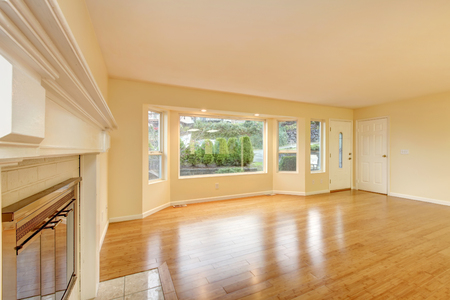 Empty living room interior with polished hardwood floor, large window and entrance door. Northwest, USA
