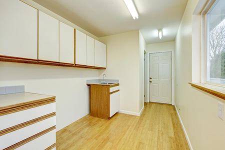 hardwood flooring: Bright laundry room interior with cabinets, sink and hardwood flooring. Northwest, USA