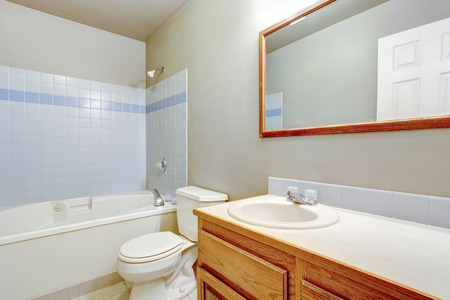 Classic American bathroom interior design with tile wall trim, white bathtub, toilet and cabinet. Northwest, USA Stock Photo