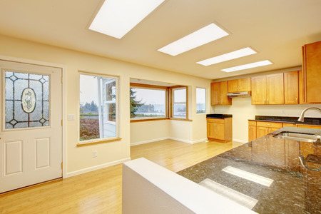 skylights: Spacious kitchen room with light brown cabinets and black granite counter tops, hardwood flooring. Also ceiling with three skylights. The kitchen has exit to back yard. Norhtwest, USA
