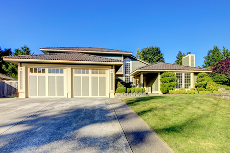 Nice curb appeal of modern gray siding house with large french windows. Two garage spaces with concrete driveway and well kept lawn.
