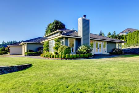 Nizza Kandareanklang der modernen blauen Abstellgleis-Haus mit gepflegtem Rasen und Sträuchern. Northwest, USA