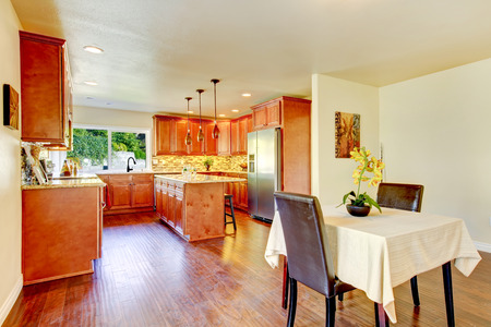 splash back: Practical kitchen with storage combination, tile back splash trim, kitchen island, pendant lights and steel appliances. View of dining table set. Northwest, USA. Stock Photo