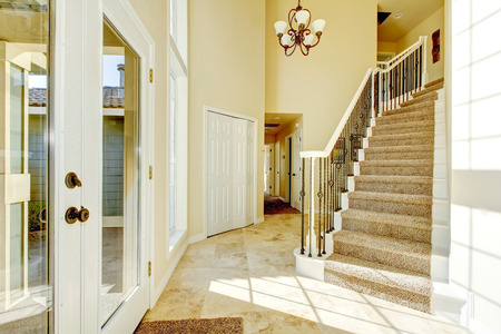 tile flooring: Bright creamy tones entryway to modern home with  tile flooring. View of carpet staircase with metal railings. Northwest, USA