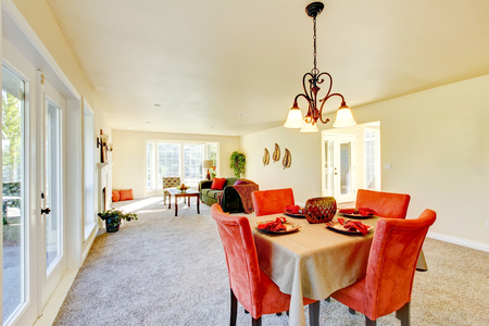 Spacious creamy tones interior of dining room with red table set and view of living room.   Northwest, USA