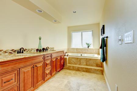 Elegant bathroom interior with large cabinet and two sinks tile trim bathtub with window. Northwest, USA