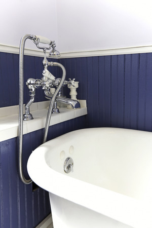 bathtub old: White tub with antique hardware and blue wood wall.