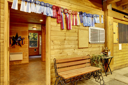 barns: Beautiful clean stable horse barn. Storage rooms with horse winners rosettes on the walls. Northwest, USA Stock Photo
